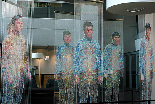 Installation view at Microsoft: Spock, Kirk, and McCoy Beaming-In (in-between), installed in front of an 8' x 12' mirror. Each figure constructed from 25,000+ colored faceted beads and silver bicone beads, monofilament, silver painted wooden dowels